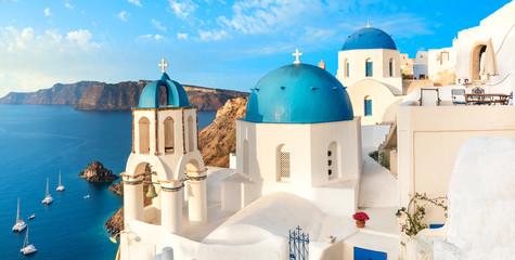 Local church with blue cupola in Oia village, Santorini island, Greece. Panoramic image with Oia skyline, volcanic caldera and blue sea