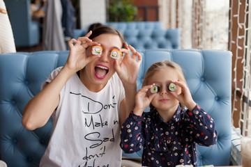 Funny mom with daughter holding sushi rolls in front of eyes.