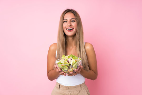 Young blonde woman with salad over isolated background