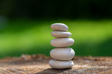 Recess Fitting Zen White stones cairn, poise light pebbles on wooden stump in front of green natural background, zen like, harmony and balance