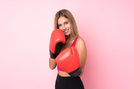 Young sport blonde woman with boxing gloves over isolated pink background