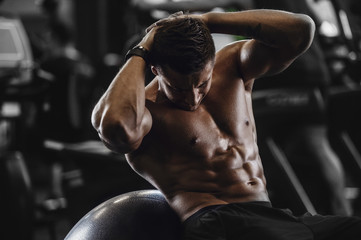 Handsome strong athletic men pumping up muscles workout fitness and bodybuilding concept background - muscular bodybuilder fitness men doing abs exercises in gym naked torso.