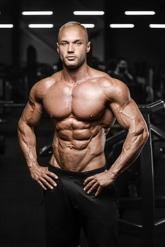 Handsome strong athletic men pumping up muscles workout fitness and bodybuilding concept background - muscular bodybuilder fitness man doing abs exercises in gym naked torso.