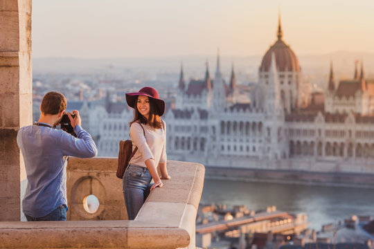 Young couple take pictures of each other on the view point from Fisherman Bastion in Budapest on sunrise.