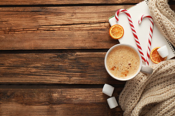 Flat lay composition with cup of coffee and sweets on wooden table, space for text. Cozy winter