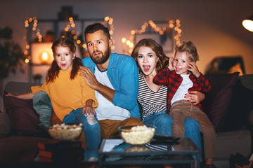 family mother father and children watching projector, TV, movies with popcorn in   evening   at...