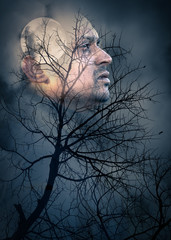 halloween theme double exposure image with male model and dark moon night behind the night tree