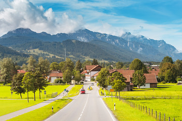 Fotobehang Alpen A picturesque and peaceful village with a road in the Alps. Travel and tourism concept