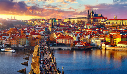 Tuinposter Praag Panoramic view above at Charles Bridge Prague Castle and river Vltava Prague Czech Republic. Picturesque landscape with sunset old town houses with red tegular roofs and broach tower.