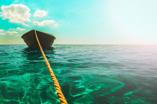 A thick clothesline is tied to an anchor that lies at the bottom of a clear blue sea, keeping the green boat on the surface in Sunny weather with clouds and glare, calm blue sea, small waves