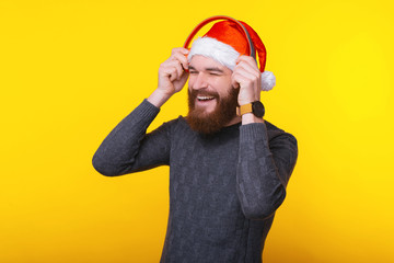 Happy man wearing santa claus hat and listening music at red headphones