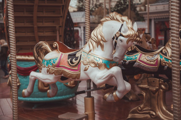 Old carousel with horses in a holiday autumn evening park with nobody