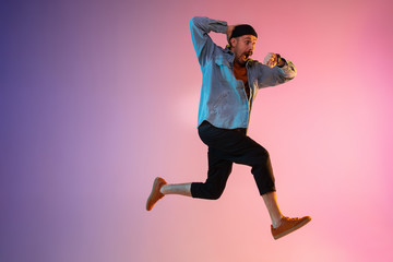 Full length portrait of happy jumping man wearing casual clothes in neon light isolated on gradient background. Emotions, ad concept. Expressive hurrying up, late for work or sale, shopping.