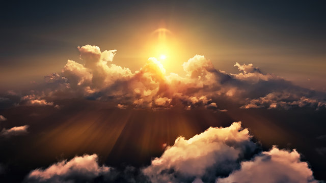 Flying through picturesque sunny cloudscape. Amazing of soft golden clouds moving in pure sunshine and the sun glowing through the clouds with beautiful rays and lens flare.