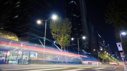 Beautiful night of Seoul road traffic, view on the busy intersection in Gangnam District. Cars, buses and other vehicles passing by creating picturesque light trails. Fotomurales