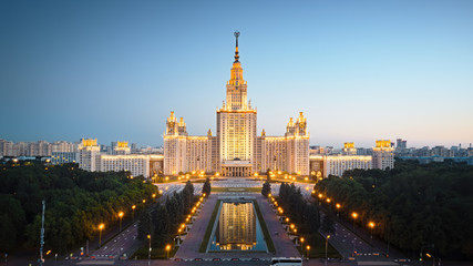 Motion of Moscow State University in the evening, aerial view. Camera moving towards MSU, showing also its alleys and outdoor lighting gradually turning on.