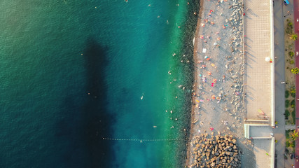 Picturesque aerial panorama of Sochi beach. Green and blue sea waves roll ashore, people swim in the water, sunbathe on the shore crammed with colorful umbrellas, and stroll along the promenade.