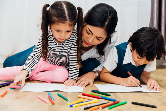 Happy child kid boy and girl kindergarten drawing on peper teacher education with beautiful mother