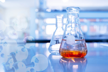 orange solution in glass flask and chemical molecular in chemistry science educational blue background