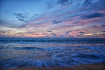 Phuket beach sunset, colorful cloudy twilight sky reflecting on the sand gazing at the Indian Ocean, Thailand, Asia. Wall mural