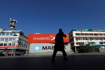 A man walks past the shipping containers placed for a roadblock ahead of Azadi March in Islamanbad,