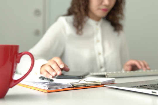 Out of focus view of businesswoman or executive working at her office table