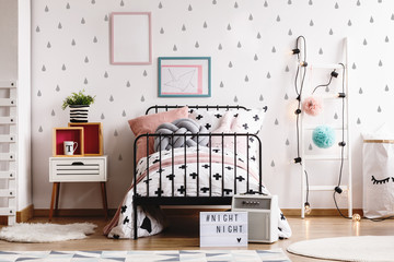 Blue and pink pompons and lights on wooden white scandinavian ladder in stylish bedroom interior with black and white bedding, small nightstand and frames on the floor