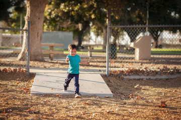 A little boy running fast into a gated playground during the fall season.