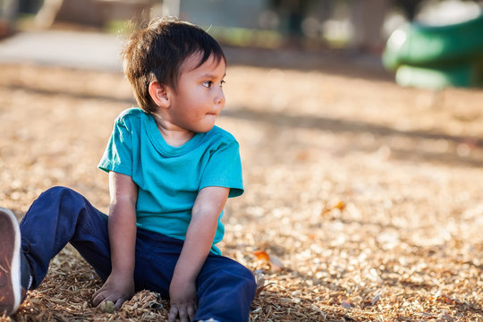 Latino boy with dirty hands from playing with woodchips from a playground all by himself and looking away.