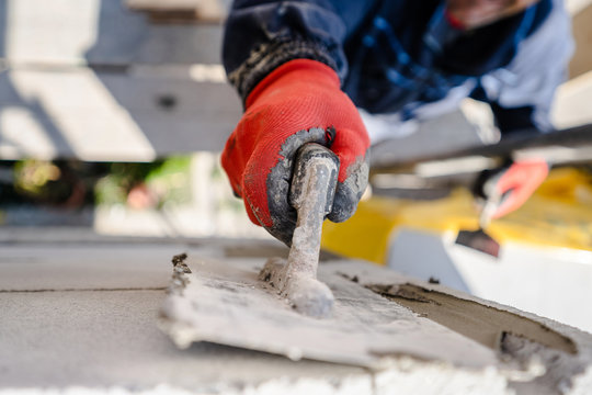 Construction worker plastering a wall with trowel cement mortar applying adhesive cement on the Autoclaved aerated concrete AAC brick high angle close up on hand holding the tool outdoor