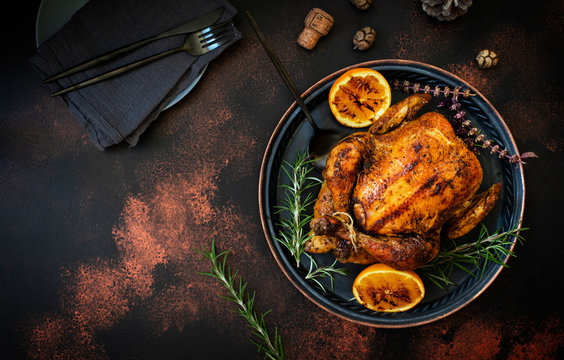 Baked whole chicken with oranges and rosemary. Tray with a festive Christmas dish on a dark rustic background. Top view, flat lay. Copyspace