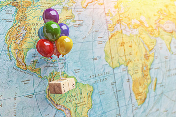 Postal express delivery service and parcels transportation, transport of purchases, logistics and business concept, package box flying on balloons in front of a world map