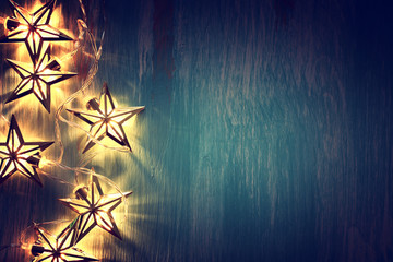 holidays concept of Christmas warm gold garland lights over wooden blue background