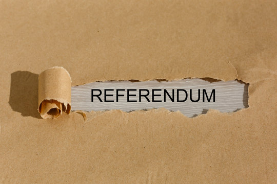 Ripped brown manilla envelope revealing the word referendum on white paper. UK Brexit deal concept
