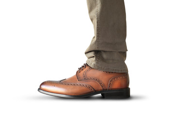A man stands in brown classic leather men's shoes
