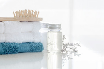 Photo sur Toile Spa Spa set with stack of clean towels, oil bottle, wooden comb and flower on white background. Copy space.