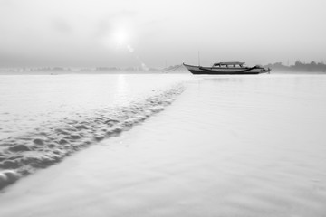 motion waterscapes of sea with beauty morning sunrise, boat in parking on sand in bengkulu, black and white photo