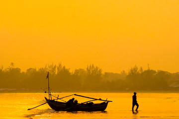 beauty morning sunrise yellow color, siluet fisherman with the boat activity