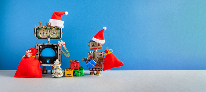 Two Santa Claus steampunk toys on blue background. Festive Christmas New year greeting card mockup with funny robots dressed red Santa hat. Mockup blue screen display, empty space backdrop for text