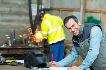 happy industrial steel welder worker at factory workshop