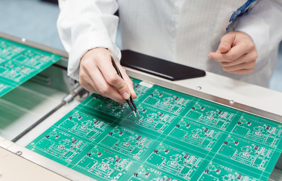 Technician assembling electronic product by inserting components into board