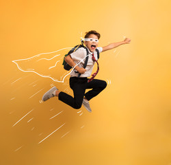 Young boy student jumps high like a super hero. Yellow background