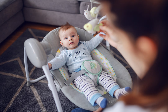 Adorable baby boy lying in bouncer an looking at his mother. Mother entertaining her loving son. Living room interior.