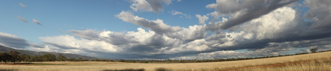 Panoramic view of large open dry drought affected farm fields under stretching cloud filled blue skies over properties in rural New South Wales, Australia