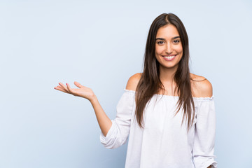 Young woman over isolated blue background holding copyspace imaginary on the palm