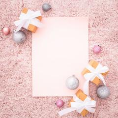 Nota en blanco en una composición navideña con tonos rosa