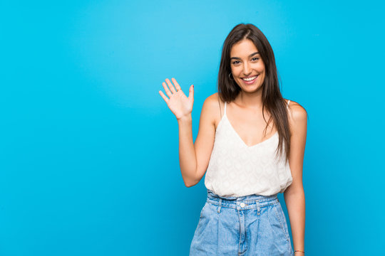 Young woman over isolated blue background saluting with hand with happy expression