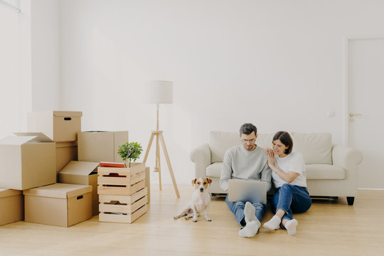 Affectionate married couple move in new home, relax on floor after unpacking things use laptop computer for searching home decoration ideas in internet their pet sits near, pose in purchased apartment
