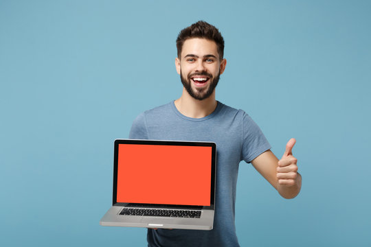 Young laughing man in casual clothes posing isolated on blue wall background in studio. People lifestyle concept. Mock up copy space. Hold laptop pc computer with blank empty screen, showing thumb up.