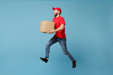 Delivery man in red uniform isolated on blue background, studio portrait. Male employee in cap...
